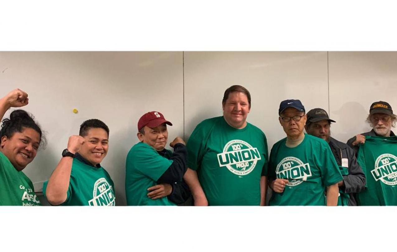 A group of Bellevue College custodians wearing WFSE shirts pose against a wall and smile.