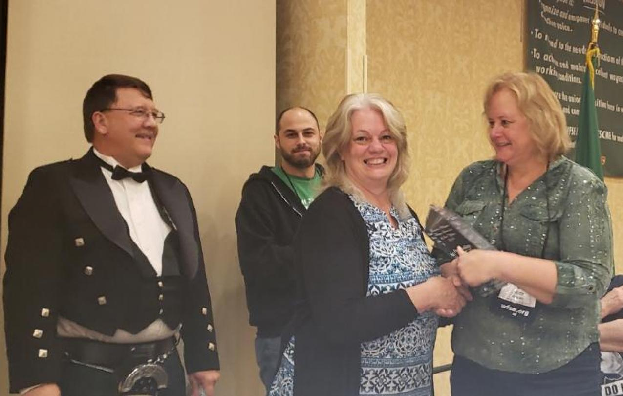 Pat Bailey shakes hands with WFSE VP Judy Kuschel, who is handing her the Laurie Merta award.